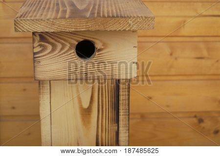 A welcoming birdhouse made of wood put up against a wooden background.