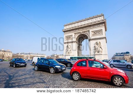 PARIS - MARCH 20: View of the Arc de Triomphe and and the traffic on the Arc de Triomphe roundabout on March 20, 2015 in Paris, France. The Arc de Triomphe is one of the main attractions of Paris.