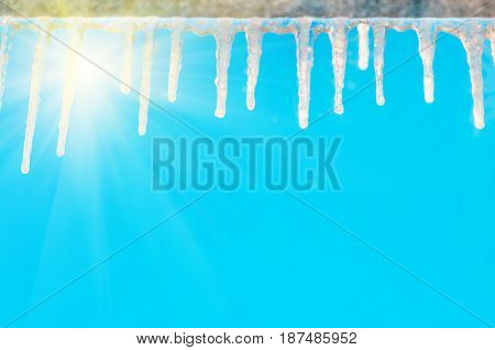 Frozen icicles hang on a cornice on a clear sunny day against a blue sky