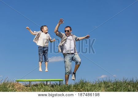 Father And Son Playing On The Field At The Day Time.