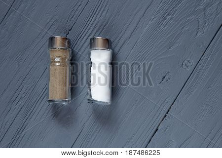 Salt and pepper set isolated on wooden background top view