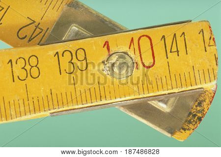 The turning point of a foldable yellow ruler in close up.