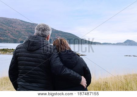 Lovely couple looking to landscape from balcony.