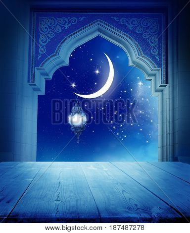 Ramadan Kareem background..Mosque window with shiny crescent moon and wooden table