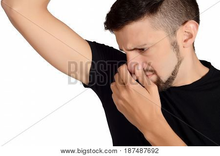 Portrait of young man smelling his armpit. Isolated white background.