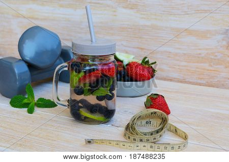 Fruit infused water with lime lemons strawberries blueberries and mint in mason jar centimeter and dumbbells on wooden background. Healthy lifestyle detox diet loss weight concept.