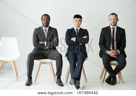Front View Of Multiethnic Businessmen Sitting On Chairs Isolated On White, Multicultural Business Te