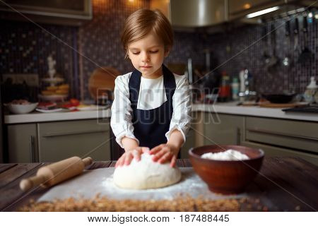 Cute little girl rolling a dough in the kitchen. Horizontal indoors shot.