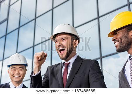 Multiethnic Group Of Excited Professional Architects In Helmets Outside Office Building, Architects