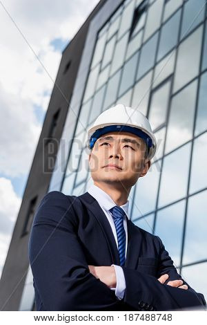 Low Angle View Of Professional Architect In Hard Hat Looking Away
