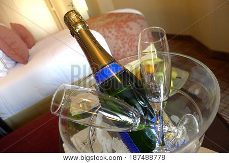 A celebratory bottle of champagne accompanied by two glasses on a bed in a hotel room.
