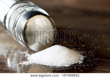 salt spilleng on a table from shaker, closeup