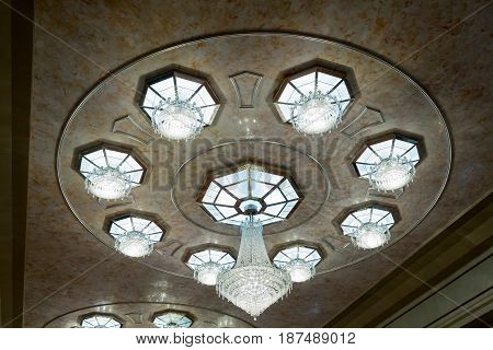 Luxurious crystal chandelier in the hall. The ceiling of the great hall