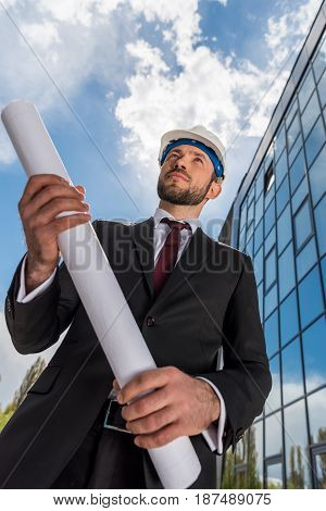 Low Angle View Of Professional Architect In Hard Hat Holding Blueprint And Looking Away