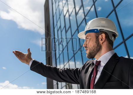 Professional Architect In Hard Hat Wearing Suit And Gesturing Outside