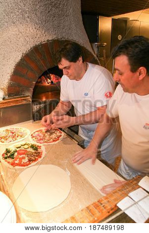 Chef Making Pizza At Kitchen Of A Restaurant At Locarno