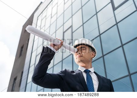 Portrait Of Professional Architect In Hard Hat Looking Through Blueprint In Hand