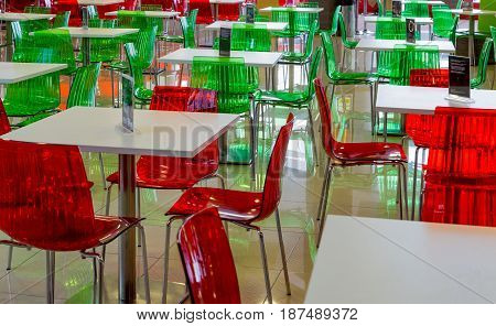 Empty tables, green and red chairs in a cafe