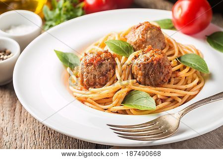 Spaghetti pasta with meatballs and tomato sauce on white plate over wooden background, close up