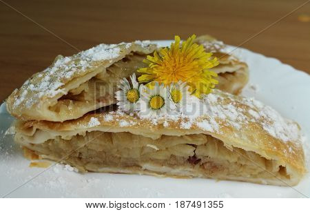 Apple strudel with raisins/ These are two pieces of apple strudel with daisy and dandelion.