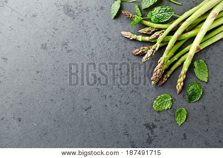 Green Asparagus and Mint Leaves on stone background