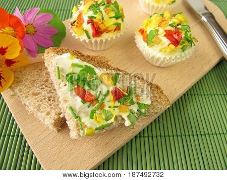 Herb butter pralines with edible flowers on bread