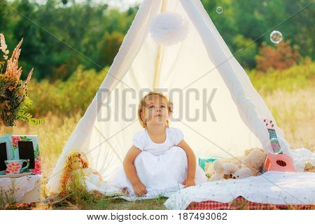 Girl in white dress sits in white tent on background of green bushes. The child sat on his haunches.