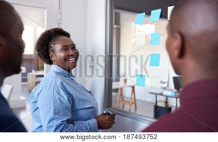Three casually dressed African work colleagues smiling and brainstorming together on a glass wall with sticky notes while standing in a modern office