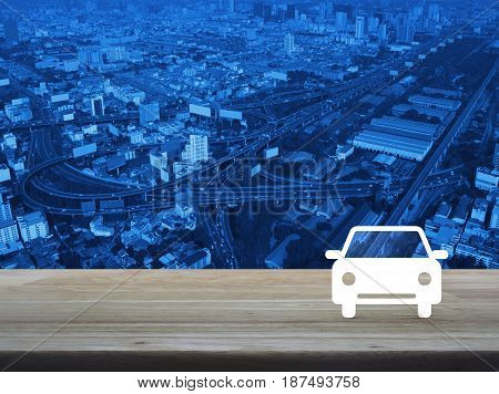 Car flat icon on wooden table over aerial of modern city tower street and expressway Business service car concept