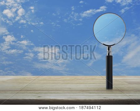 Magnifying glass on wooden table over blue sky with white clouds Business analyzing concept