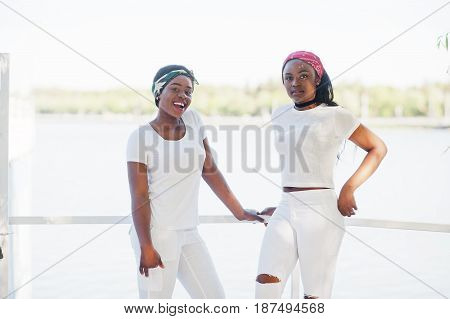 Two Stylish And Trendy African American Girls, Wear On White Clothes Against Lake. Street Fashion Of