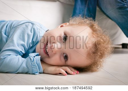 Little girl with curly hair winks. Child lying on a sofa. Portrait of a young smiling happy baby girl. cute toddler with amazed smiling face