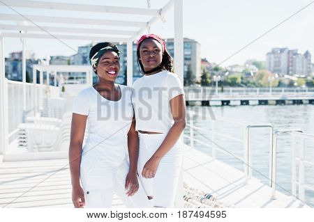Two Stylish And Trendy African American Girls, Wear On White Clothes Against Lake On Pier Beach. Str