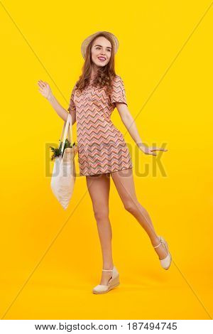 Pretty cheerful woman posing with bag of products. Vertical studio shot.