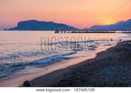 Beach of  Alanya  at  the sunset, Turkey.  At the background  Alanya Peninsula