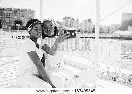 Two Stylish And Trendy African American Girls, Wear On White Clothes Against Lake On Pier Beach Maki
