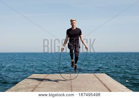 Young sportive man doing rope jumping on concrete pier with sea on background.