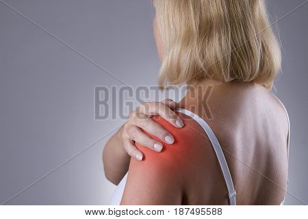 Pain in shoulder care of female hands ache in woman's body on gray backgroun
