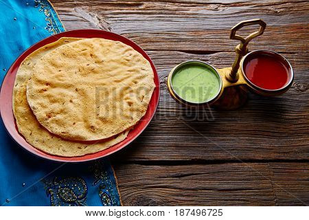 Appalam or Papadam brad with red and green sauces from Indian food papad