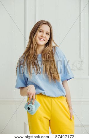 Smiling girl in casual cloth stands with camera in hand on background of wall. Young woman with long hair dressed in blue t-shirt and yellow trousers, person in good mood