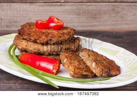 liver pancakes or cutlets with chili pepper and green onions on a wooden background.