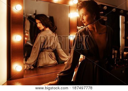 Beautiful sexy girl near the mirror in the dressing room in a gray silk dressing gown