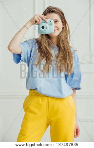 Smiling girl in casual cloth makes photo by portative camera on background of wall. Photographer young woman with long hair dressed in cosy home clothes posing in blue t-shirt and yellow trousers,