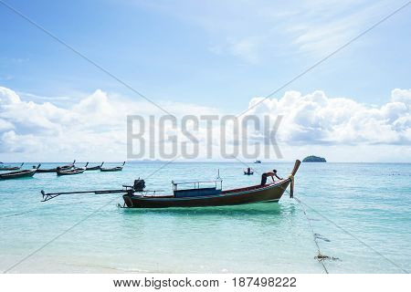 fisherman anchor long tail boat on the blue sea with bright sunshine
