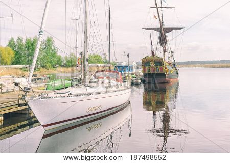 Vintage wooden sail boat moored next to the modern yacht at a mooring on the river in summer day