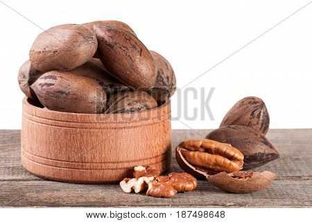 pecan nuts in a wooden bowl on the old board.