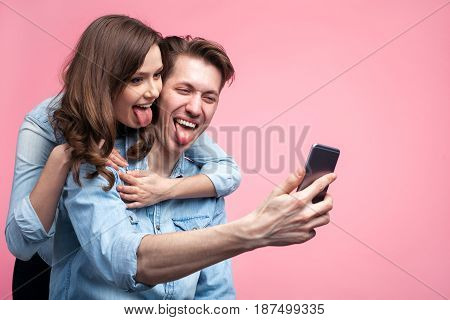 Loving cheerful couple having fun while taking selfie on pink background.