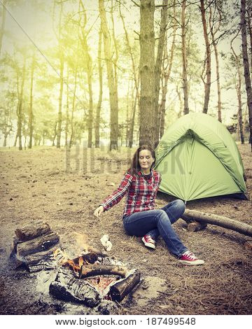 The girl is sitting near the campfire at the campsite and frying marshmallows.