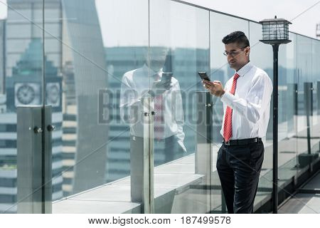 Businessman using a mobile phone on the top of a modern office building