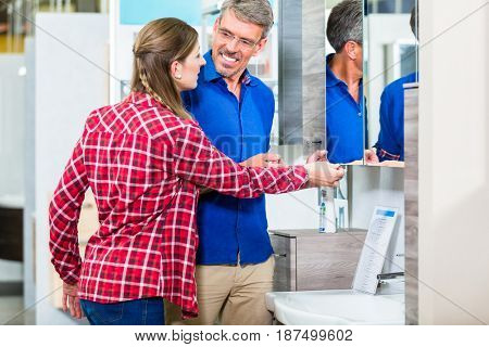 Shop assistant in hardware store counseling customer about lavatories for do-it-yourself project